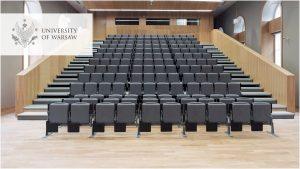 Sala wykładowa na Wydziale Nauk Politycznych i Studiów Międzynarodowych. Logo UW w wersji angielskiej w lewym górnym rogu