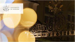 brama UW wieczorowa porą, w odcieniach żółci, logo UW w wersji angielskiej w lewym górnym rogu